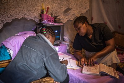 Florian helping her daughter Sheila Achieng do her revision at home in Kibera as schools are closed due to the Covid-19 pandemic (file photo).