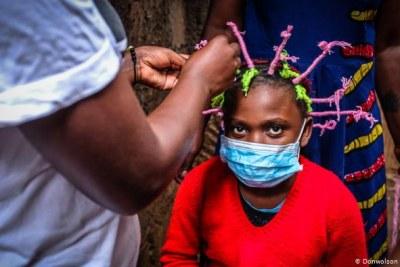 Non seulement Mable Etambo a conçu la coiffure en forme de coronavirus, mais elle utilise également un fil mulyicolore  pour représenter les couleurs du virus lui-même.