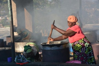 Women prepare porridge at a primary school in Malawi (file photo).