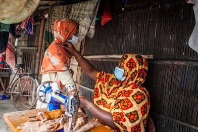 Une femme tailleur établie dans une cité rurale africaine