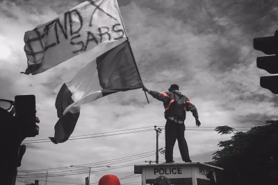A protester stands on a police structure in Ikeja, capital of Lagos state, during #EndSARS demonstrations on October 11, 2020.
