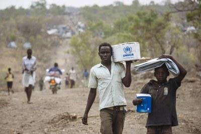 Des réfugiés sud-soudanais avec des articles de secours dans le site pour réfugiés de Bidibidi, en Ouganda.