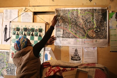 Blessing Nyoni pins a map to the wall that shows the informal settlement of Bhambayi near Phoenix. About 70 families live in this area.